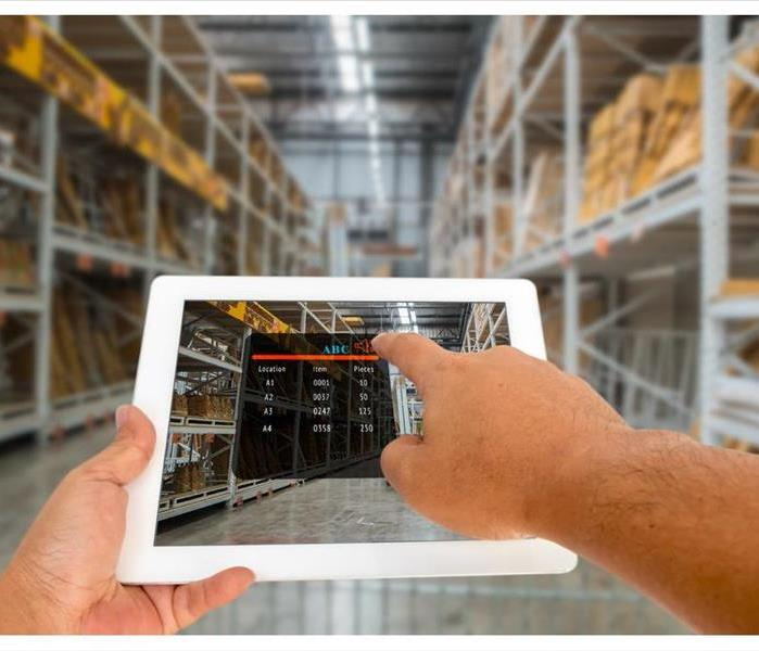 Hand hold and touching digital tablet with smart inventory application on screen in the warehouse.