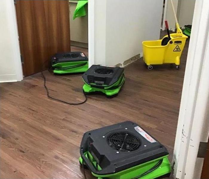 three green air movers placed on the drying, drying a space that has been damaged by water.